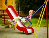 stock photo of swings  - Happy little girl looking at camera while swinging on playground area - JPG