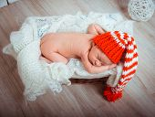 Cute newborn baby sleeps in a santa claus hat close-up