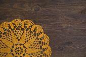 Yellow crochet doily over dark wood