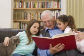 stock photo of storytime  - grandfather reading a story to his grandchild with a cat - JPG