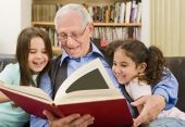 image of reading book  - grandfather and grandchildren reading a book at home - JPG