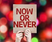 Now Or Never card with colorful background with defocused lights