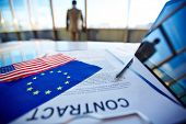 Text of contract with pen, touchpads, American flag and that of European Union with male entrepreneur on background