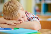 Tired little lad napping by desk in classroom