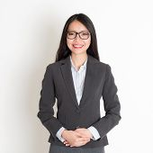 Asian business woman smiling at camera, standing on plain background.
