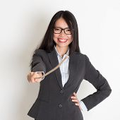 Asian female teacher smiling and holding a stick pointing at camera, standing on plain background.
