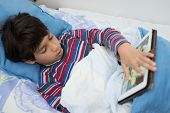 Child patient in hospital bed using tablet