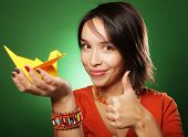 young expression woman with paper bird over green background
