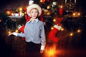 Cute seven year old boy stands with gifts by the fireplace at home. He is surprised. The magic of Christmas.