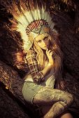 Attractive modern girl in style of the American Indians. Western style. Jeans fashion. Tattoo.