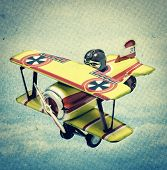 retro tin toy plain with clouds and sky , retro styled image .