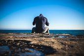 athlete taking break sitting on rocks with sea horizon