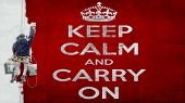 Building painter hanging from harness painting a red wall with white letters the motto Keep calm and carry on