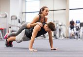 fitness, sport, training, teamwork and lifestyle concept - smiling couple doing push-ups in the gym