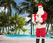 christmas, holidays, travel and people concept - man in costume of santa claus with gift box over tropical beach and swimming pool background