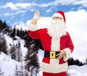 christmas, holidays, gesture and people concept - man in costume of santa claus waving hand over snowy mountains background