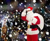 christmas, holidays and people concept - man in costume of santa claus with bag looking far away over snowy night city background