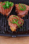 fresh grilled beef fillet strips on black grill plate over wood