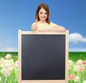 people, advertisement and education concept - happy little girl with blank blackboard showing thumbs up