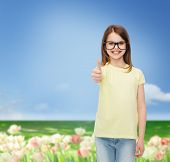 education, school and vision concept - smiling cute little girl in black eyeglasses showing thumbs up