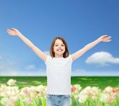 advertising, childhood, nature, gesture and people concept - smiling girl in white t-shirt with stretched out arms over field background