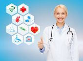 healthcare, medicine, people, gesture and symbols concept - smiling young female doctor or nurse with stethoscope showing thumbs up over medical icons and blue background