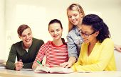 education and school concept - four smiling students with textbooks and books at school