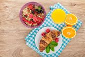 Healthy breakfast with muesli, berries, orange juice and croissant. On wooden table