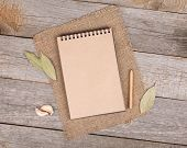 Blank notepad for copy space and herbs on wooden table