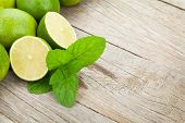 Fresh ripe limes with mint on wooden table with copy space