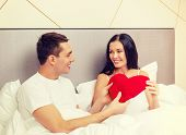 hotel, travel, relationships, holidays and happiness concept - smiling couple in bed with red heart-shaped pillow