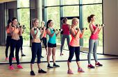 fitness, sport, training, gym and lifestyle concept - group of women with dumbbells in gym
