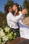 Young caucasian couple wedding portrait in the park. Focus on the bunch of flowers