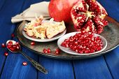 Juicy ripe pomegranates on wooden table