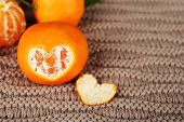 Juicy ripe tangerines on knitted background