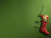 Christmas sock with red gift box on green paper background
