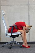 relax on armchair in office - business woman in red dress  exercising