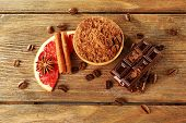 Bowl of cocoa with chocolate, coffee beans and slice of grapefruit on rustic wooden background