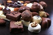 Group of sweet chocolate truffles on the dark wooden smooth background