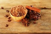 Bowl of cocoa with spices and coffee beans on wooden background