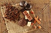Pile of coffee beans with chocolate, nuts and cinnamon on burlap cloth on wicker mat