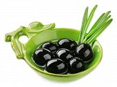 Oil and black olives in small green saucepan with long leaves isolated on white