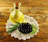 Composition of small round plate with black olives near oil can on lace doily, on rustic wooden table, on burlap background
