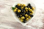 Plate in the form of heart with black and green olives on painted wooden background