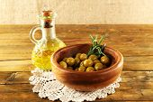 Composition of round bowl with green olives near oil can on lace doily, on rustic wooden table, on burlap background