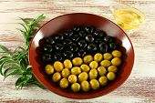 Black and green olives in bowl with branch on painted wooden background