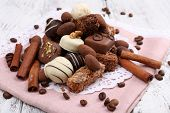 Heap of sweet chocolates with coffee beans on pink material and white doily on wooden background