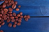 Spilled coffee beans on blue wooden background