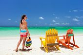 Young woman enjoying vacation at tropical beach with two colorful wooden chairs on white sand and turquoise ocean water