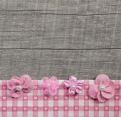 Four pink handmade flowers on wooden grey shabby chic background for a greeting card.